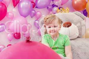 Neat little girl posing in studio with balloons