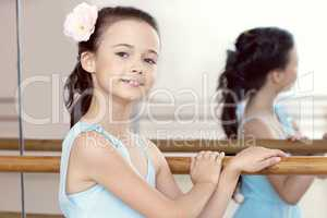 Portrait of adorable ballerina posing with barre