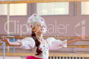 Artistic young ballerina posing in Russian costume