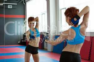 Amusing girl photographing herself in mirror