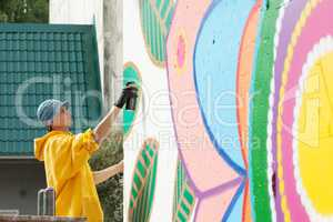 Creative young man drawing with spray can on wall