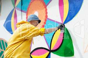 Focused young man painting graffiti on wall