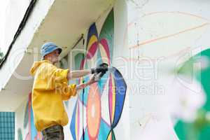 Image of man paints on wall with spray can
