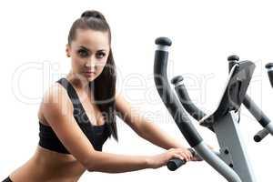Portrait of hot girl exercising on ski simulator