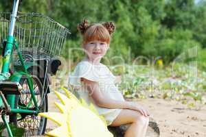 Funny red-haired little girl posing with bicycle