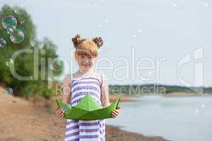 Playful girl posing with paper boat and bubbles