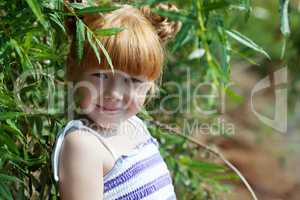 Shy red-haired girl posing with tree