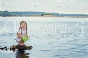 Cute girl preparing to launch paper boat at lake