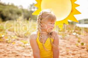 Tanned little blonde posing on sun background