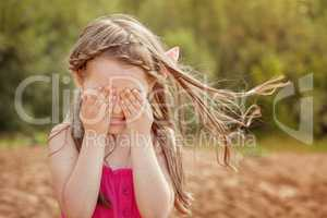 Cute little girl playing hide and seek with camera