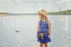 Funny blonde girl posing on background of lake