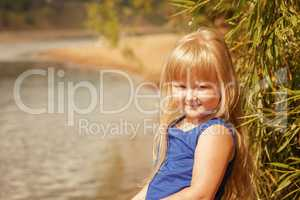 Portrait of little blond girl on vacation in park