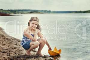 Cute girl posing with homemade paper boat by lake