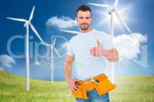 Composite image of handyman wearing tool belt with thumbs up