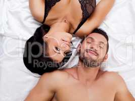 Attractive sexual partners lying on satin sheets