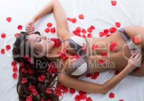 Dreamy model luxuriating on sheet with rose petals