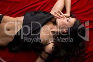 Top view of seductive brunette lying on red sheet