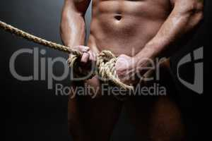Studio shot of naked strong man tied with rope