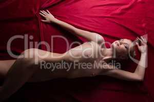 Fascinating girl posing nude on satin bedsheet