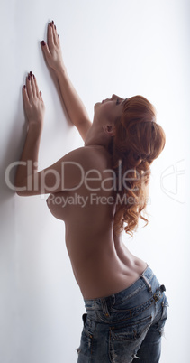 Busty red-haired model posing topless