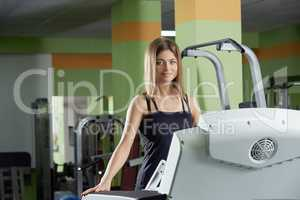 Image of pretty blue-eyed girl trains in gym