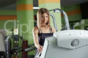 Lovely girl posing at camera while training in gym