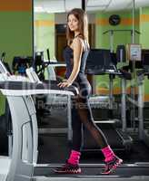 Smiling girl posing while training on treadmill