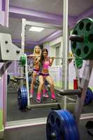 Girl trains with barbell and her girlfriend helps