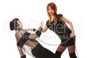 Redhead dominatrix keeps chained submissive girl