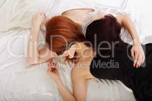 Sexual girlfriends hugging while lying in bed