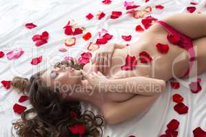 Fascinating topless girl lying with rose petals