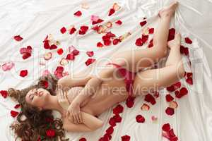 Top view of seductive topless model with petals