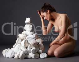 Nude woman telekinetically moving stones in studio
