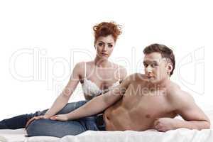 Attractive young heterosexual pair posing in bed