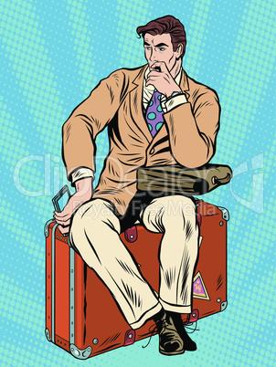 Man traveler sitting on a suitcase