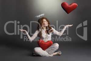 Studio shot of feminine angel playing with hearts