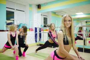 Gym. Alluring female athletes warming up