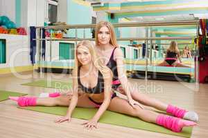 Image of sexy blondes doing splits in gym