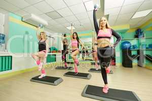 Pilates. Cute girls training on steppers
