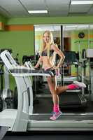 Gym. Graceful female athlete posing on treadmill