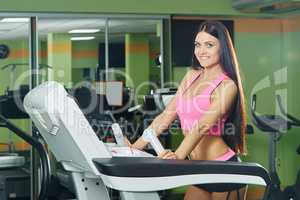 Gym. Sexy brunette exercising on treadmill