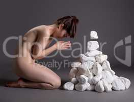 Meditation. Nude girl moving stones mentally