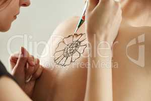 Mehndi master drawing with henna on model's back