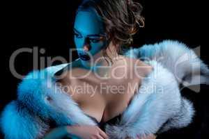 Luxury woman with deep neckline posing in fur