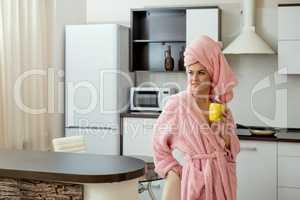Pretty woman drinking tea in kitchen after bath