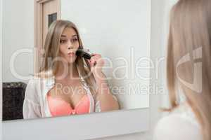 Reflection in mirror of funny girl applying powder