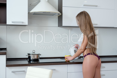 Kitchen. Sexy girl in lingerie pours hot water