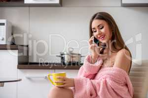 Woman talking on cellular while having breakfast