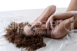Curly-haired model posing at camera while lying