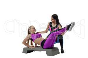 Fitness coach helping girl do exercise on stepper